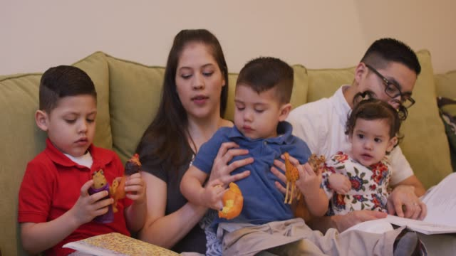 Hispanic Family Sitting and Reading Together Hispanic mother and father read to their kids as they sit on a sofa and play with toys latin american and hispanic ethnicity stock videos & royalty-free footage