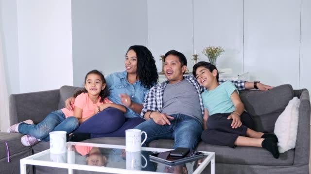 Hispanic familie TV kijken samen in de woonkamer video