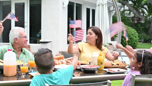 Hispanic family waving American flags celebrating Fourth of July Three generation family enjoying barbecue meal together waving stars and stripes family 4th of july stock videos & royalty-free footage
