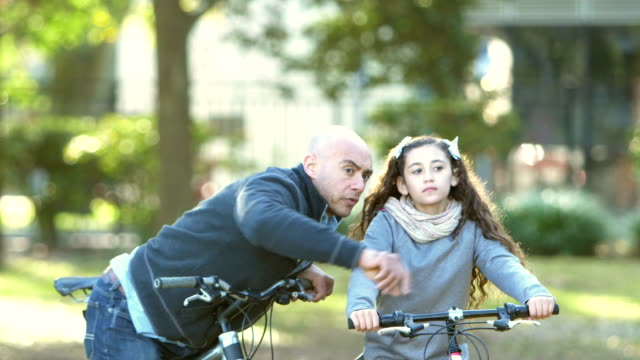 Hispanic father and daughter riding bikes in park