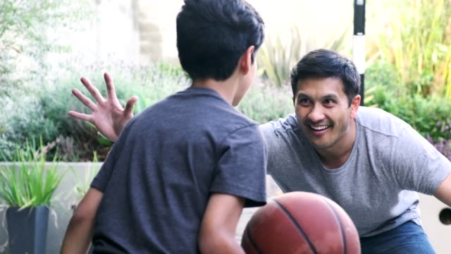 Hispanic father and son playing basketball together outdoors Hispanic father and son playing basketball together outdoors latin american and hispanic ethnicity stock videos & royalty-free footage