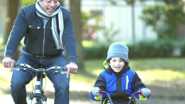 vídeos y material grabado en eventos de stock de padre e hijo hispanos montando bicicletas en el parque - abrigo