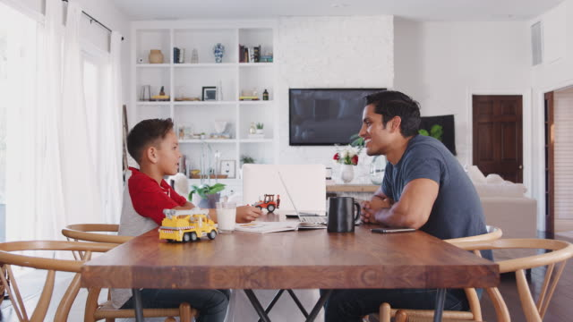 Hispanic father and son talking while they work sitting at the dining table, side view