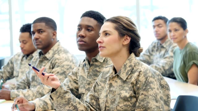 Hispanic female cadet asks question during army training class Attentive young female cadet gestures with a pen as she asks a question during class at a military academy. She pauses to listen to the answer and then nods her head in agreement. army stock videos & royalty-free footage