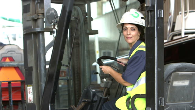 Trabajador de la construcción femenina sube a la carretilla elevadora - vídeo