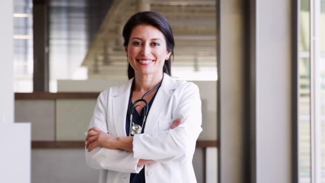hispanic female doctor wearing a lab coat - portret do pasa filmów i materiałów b-roll