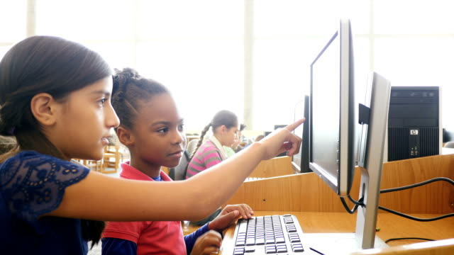 A Hispanic female middle school student tutors an African American female elementary student on a computer at STEM school Cute Hispanic middle school student is tutoring a young African American female elementary student in the computer lab or library of their STEM school. The Hispanic girl points at the screen as she explains the information. She also shows the younger student the keys on the keyboard. The younger girl types and then points at the computer monitor. Students are working on computers in the background. Books are on bookshelves in the background. A handheld camera focuses on the students. elementary age stock videos & royalty-free footage
