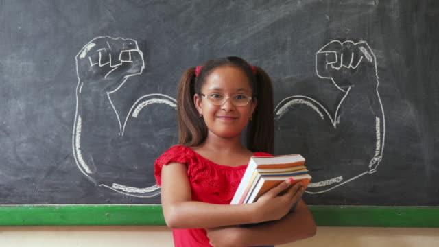 vídeos y material grabado en eventos de stock de chica hispana sosteniendo libros en el aula y sonriendo - fuerza