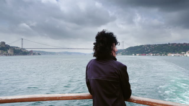hispanic girl looks at the suspension bridge across the bosphorus standing on boat deck during tourist tour cruise on bosporus strait - passenger craft stock videos & royalty-free footage
