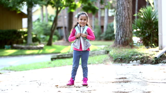 Hispanic girl ready for preschool A 4 year old Hispanic girl standing outdoors, outside her home, ready for preschool, carrying a backpack, smiling at the camera. full length stock videos & royalty-free footage