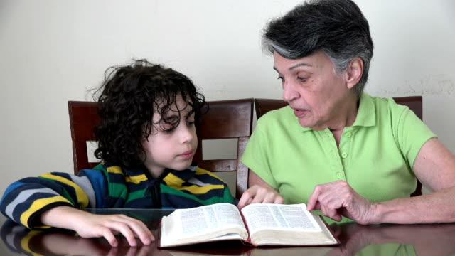 Hispanic grandmother and grandson studying the Bible video