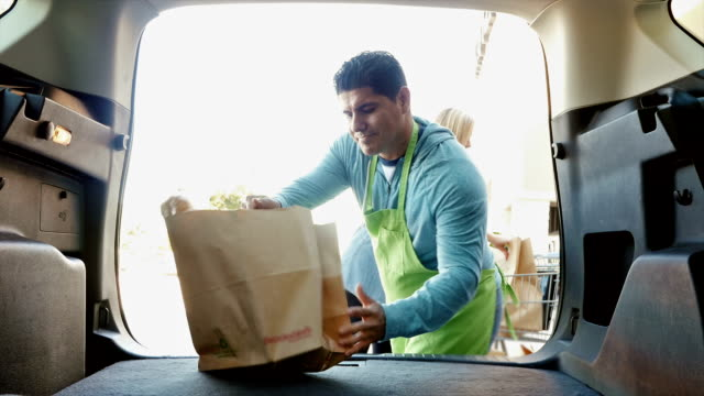 Hispanic grocery store employee is helping mother and daughter load grocery bags in SUV or minivan video