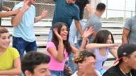 istock Hispanic male and female teenagers cheering from bleachers 1204641510
