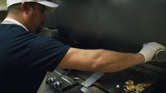 vídeos de stock e filmes b-roll de hispanic male cook in his thirties sprinkles seasoning before stirring vegetables on a griddle at a mexican restaurant - characters