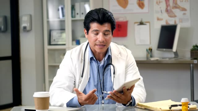 hispanic male doctor video conferences with patient - telemedicine stock videos & royalty-free footage