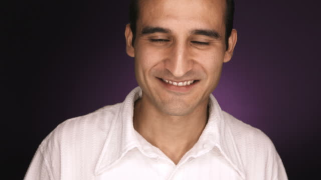 Hispanic male smiles for the camera with purple background video
