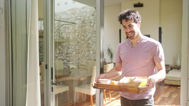 vídeos de stock e filmes b-roll de hispanic man bringing breakfast to the table - mesa mobília