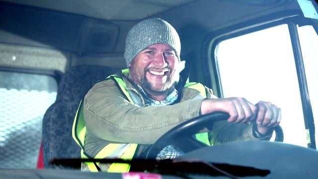 Hispanic man driving truck, buckles his seat belt