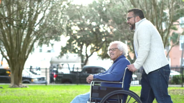 Hispanic man pushing senior father in wheelchair A senior Hispanic man in his 80s sitting in a wheelchair, talking to his adult son, who is in his 30s, pushing the wheelchair from behind. They are walking in a city park in fall, wearing sweaters and jeans. pushing wheelchair stock videos & royalty-free footage