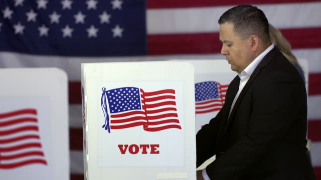 Hispanic man voting at booths at polling station video