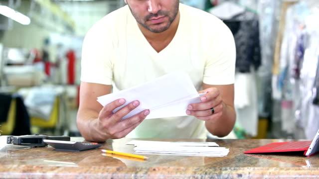 Hispanic man working at dry cleaners paying bills video