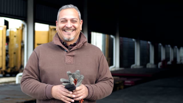 Hispanic man working at train loading dock A mature Hispanic man in his 40s working at a railway loading dock, smiling at the camera. manual worker stock videos & royalty-free footage