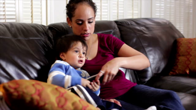 Hispanic mom watching TV with her son video