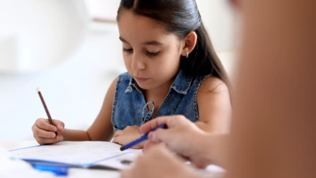 hispanic mother helping girl doing school homework at home - writing class stock videos and b-roll footage