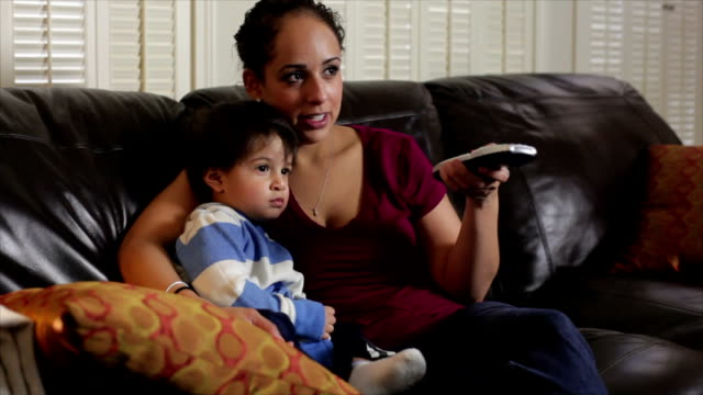 Hispanic mother watching TV with her son. video
