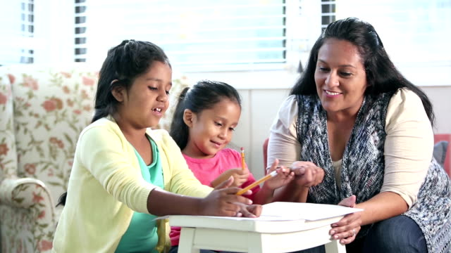Hispanic mother with daughters doing homework