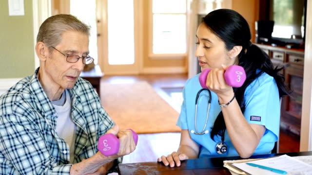 vídeos de stock, filmes e b-roll de enfermeira espanhola ajuda paciente sênior com pesos de mão durante a visita domiciliar - assistência à terceira idade