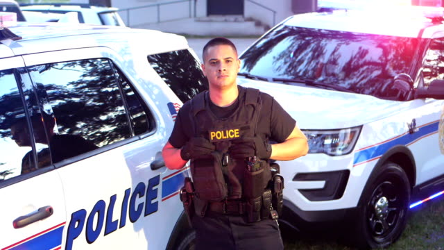 hispanic officer standing by police cars - police officer stock videos and b-roll footage