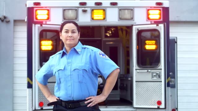 hispanischer sanitäter steht vor krankenwagen - held stock-videos und b-roll-filmmaterial