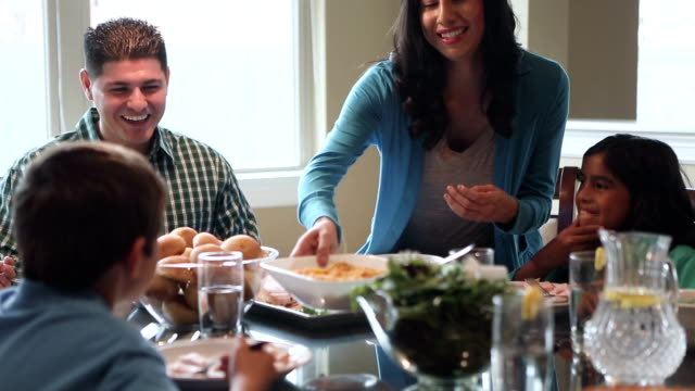 Hispanic parents having meal with children around dinner table at home video