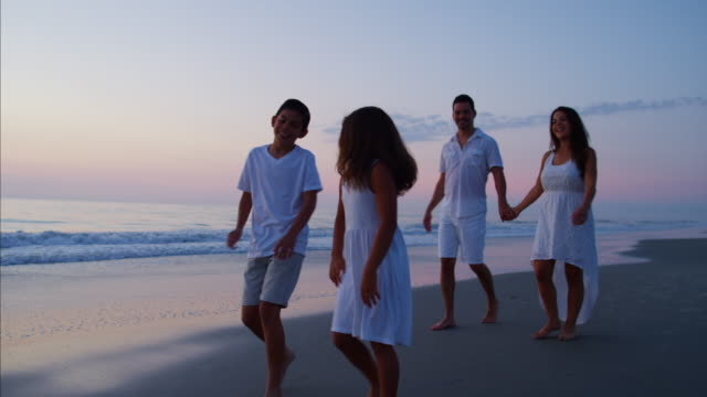 Hispanic parents with kids by ocean at sunset
