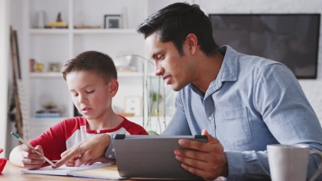 hispanic pre-teen boy sitting at dining table working with his home school tutor, close up - preadolescente video stock e b–roll