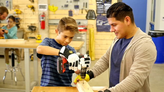 Hispanic preteen boy working with power tool at community woodworking day camp video