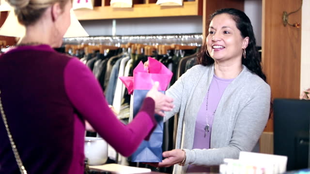 Hispanic saleswoman in clothing store helps customer pay A mature Hispanic woman in her 40s, owner of a successful small business, a women's clothing store, smiles as she helps a customer make a purchase. She returns the buyer's credit card and hands her a shopping bag. saleswoman stock videos & royalty-free footage