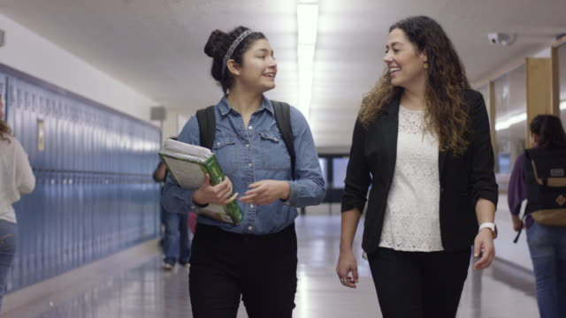 Hispanic Student Walking The Halls with Her Teacher A Hispanic Female student walks the halls with her high school teacher guidance stock videos & royalty-free footage