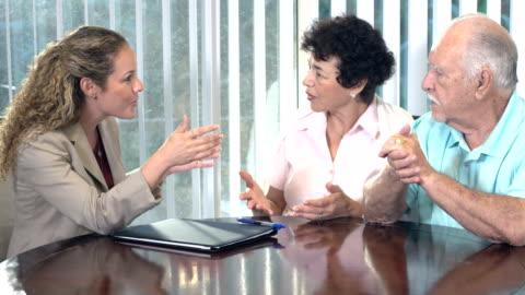 donna ispanica che consiglia la coppia anziano in casa - abbigliamento casual video stock e b–roll