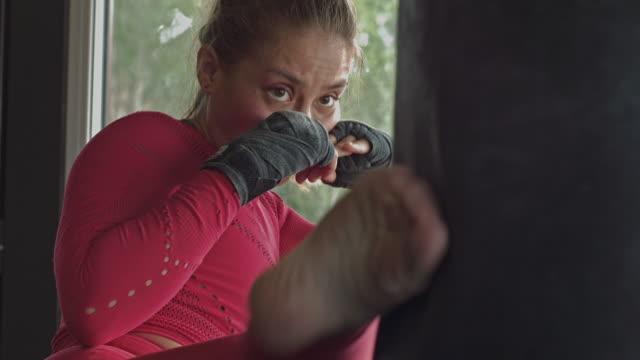 hispanic woman boxing a punching bag fighting fiercely - sacco per il pugilato video stock e b–roll
