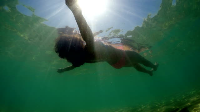 Hispanic woman floats and plays in a sea backlit by sun rays, underwater view Hispanic woman floats and plays in a sea backlit by sun rays, underwater view florida us state stock videos & royalty-free footage