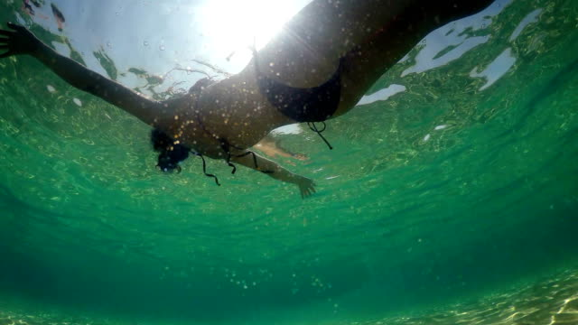 hispanic woman floats and plays in a sea backlit by sun rays, underwater view - grecia stato video stock e b–roll