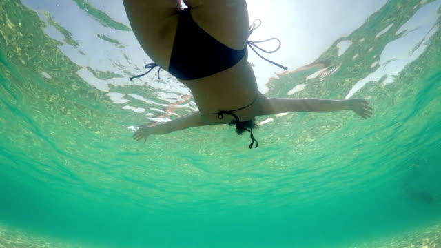 hispanic woman floats and plays in a sea, underwater view - grecia stato video stock e b–roll