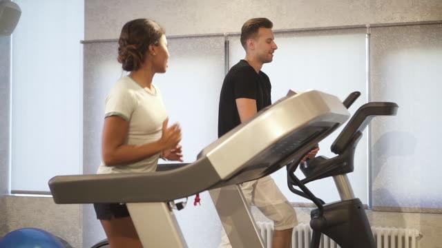 spansktalande kvinnan är utbildning på löpband, prata och flirta med stark leende man jogging nära - gym skratt bildbanksvideor och videomaterial från bakom kulisserna