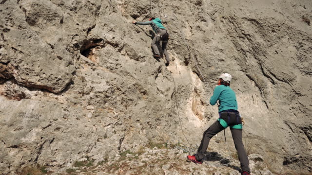 Hispanic woman on adventurous  rock climbing video