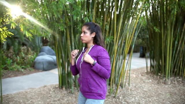 Hispanic woman power walking in park video