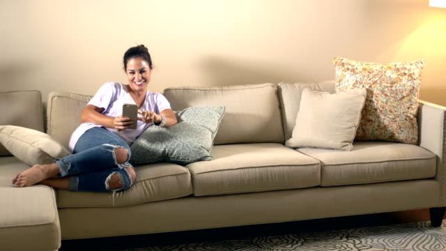 Hispanic woman relaxing on coach, using smart phone