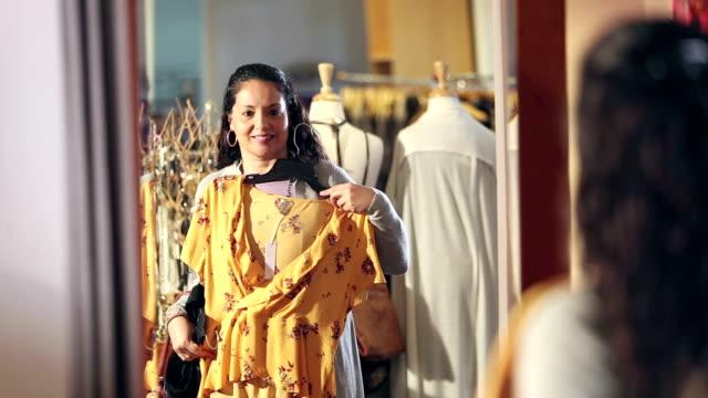vídeos y material grabado en eventos de stock de mujer hispana comprando en tienda de ropa, en espejo - vestimenta