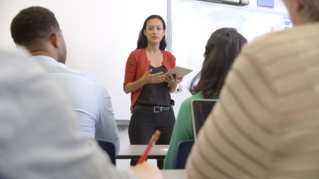 hispanic woman with tablet teaching adult education class - classroom stock videos and b-roll footage